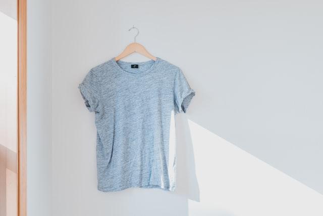 niebieski t-shirt wiszący na wieszaku na tle białej ściany