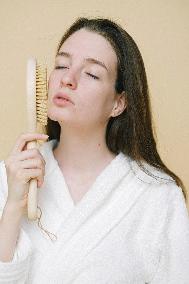 kobieta masuje szczotką twarz i nie ma na sobie makijażu