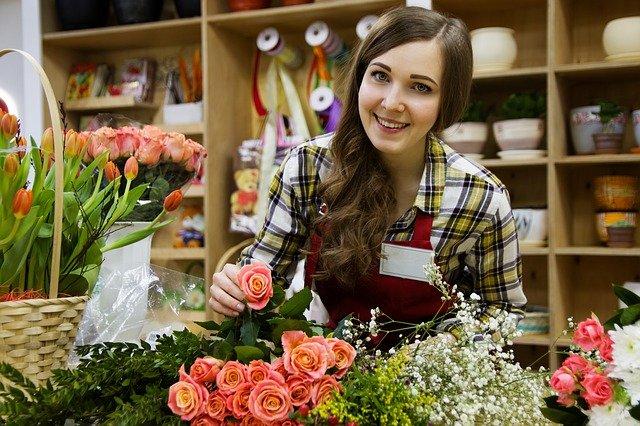 uśmiechnięta szatynka w rozpuszczonych włosach i koszuli w kratę stoi za ladą, na której leżą kolorowe kwiaty