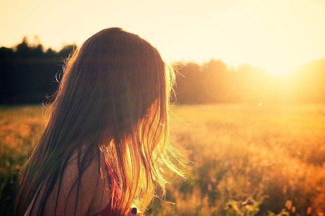 dziewczyna w rozpuszczonych włosach na łące stoi bokiem na tle zachodzącego słońca