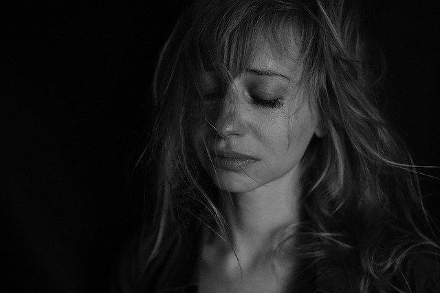 zapłakana kobieta z zamkniętymi oczami i rozmazanym makijażem na czarno-białym zdjęciu