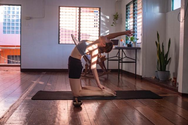 kobieta w sportowym stroju ćwiczy na macie w domu