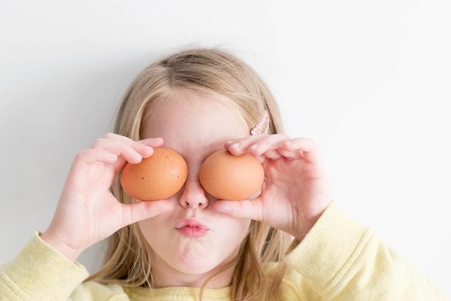 dziewczynka o blond włosach przykłada jajka do oczu i robi śmieszną minę