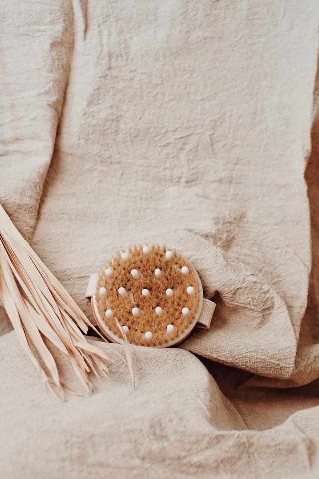 szczotka do masażu położona na tle lnianego materiału