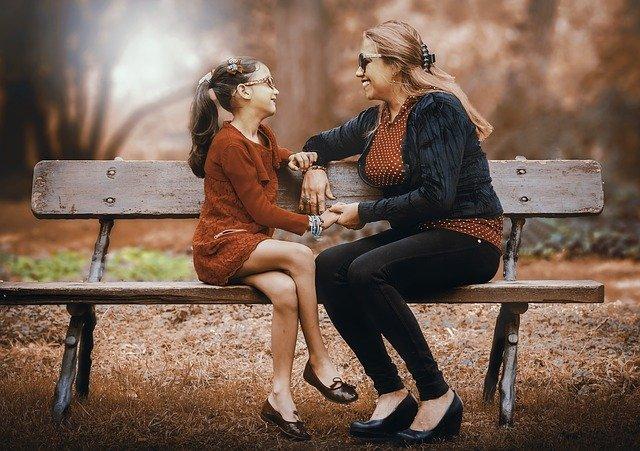 mama z kilkunastoletnią córką siedzą na ławce do siebie przodem i śmieją się