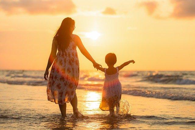 kobieta w długich włosach i luźnej sukience trzyma za rękę chłopca i idą brzegiem morza przy zachodzącym słońcu