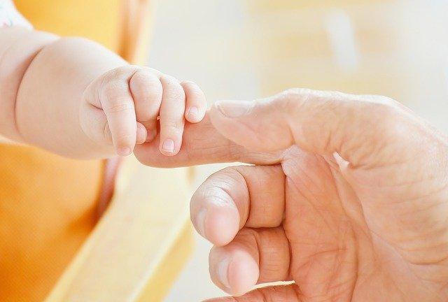 mała rączka trzyma dorosłą rękę