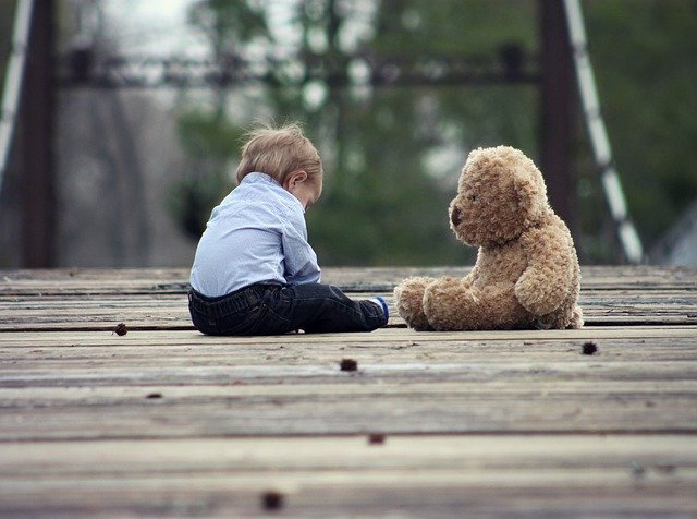 mały chłopiec z blond włosami w niebieskiej koszuli siedzi na drewnianej podłodze obok misia
