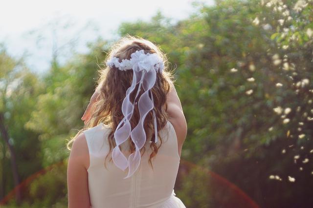 dziewczynka w rozpuszczonych włosach i wianku na głowie stoi tyłem na tle zielonych krzaków w białej sukni komunijnej