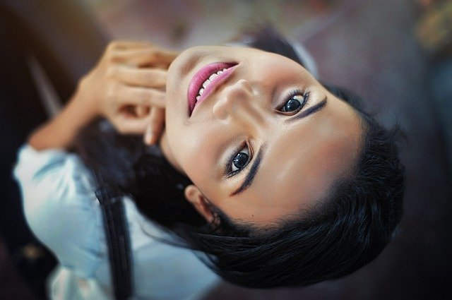 brunetka spogląda do góry, siedząc na ziemi
