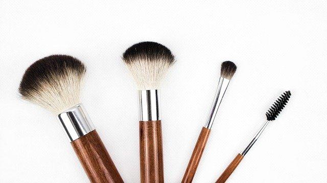 pędzle do makijażu z drewnianą rączką leżą obok siebie na białym tle