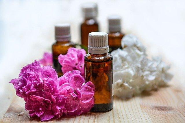 szklane, brązowe buteleczki stoją między różowymi i białymi kwiatkami