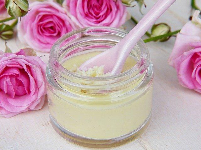 słoik z olejem kokosowy stoi na białym blacie obok różowych róż
