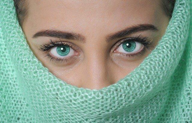 Zbliżenie na niebieskie oczy kobiety i ciemne brwi, która na nosie ma turkusowy szalik