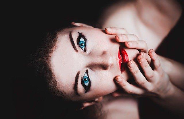 zbliżenie na twarz mocno umalowanej brunetki z niebieskimi oczami