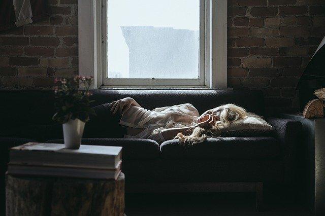 kobieta leżąca w ciemnym pomieszczeniu w pokoju