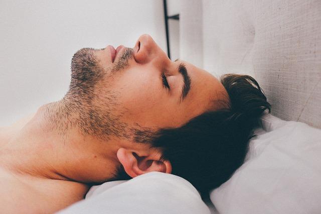 zbliżenie na profil mężczyzny leżącego na plecach w łóżku