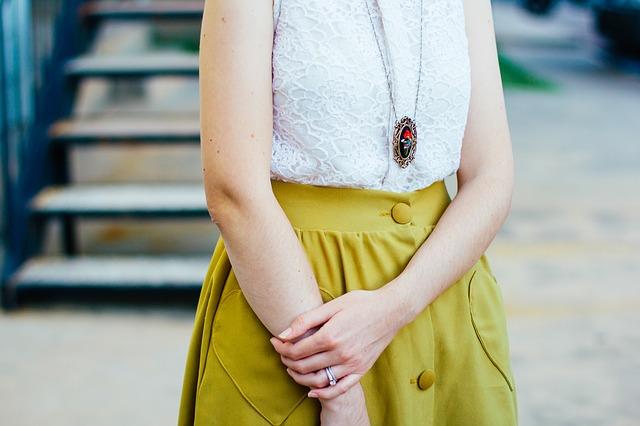 tułów kobiety w białej bluzce i limonkowej spódniczce
