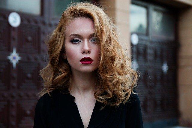 rudowłosa kobieta z włosami do ramion z umalowanymi na czerwono ustami
