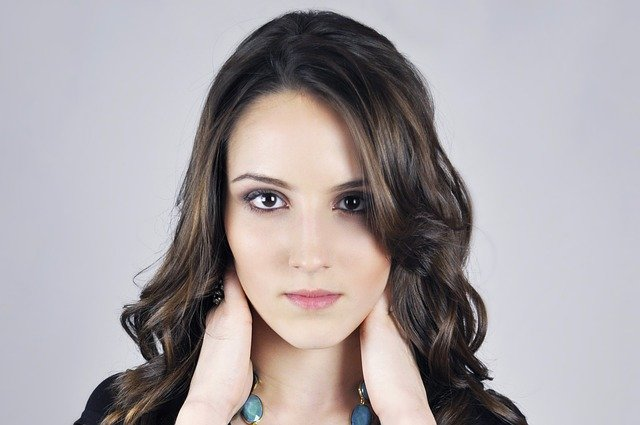 zdjęcie portretowe brunetki z rozpuszczonymi włosami i pełnym makijażu, która łapie się za szyję