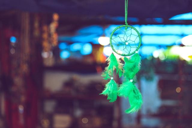 wiszący, zielony łapacz snów na rozmytym tle