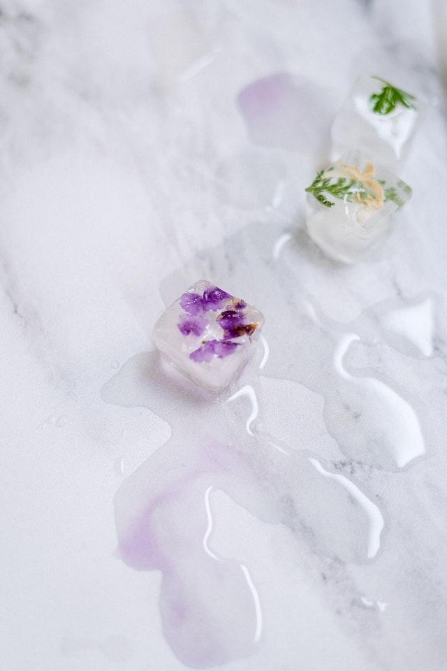 rozpuszczające się kostki lodu z kwiatami rozrzucone na jasnym blacie