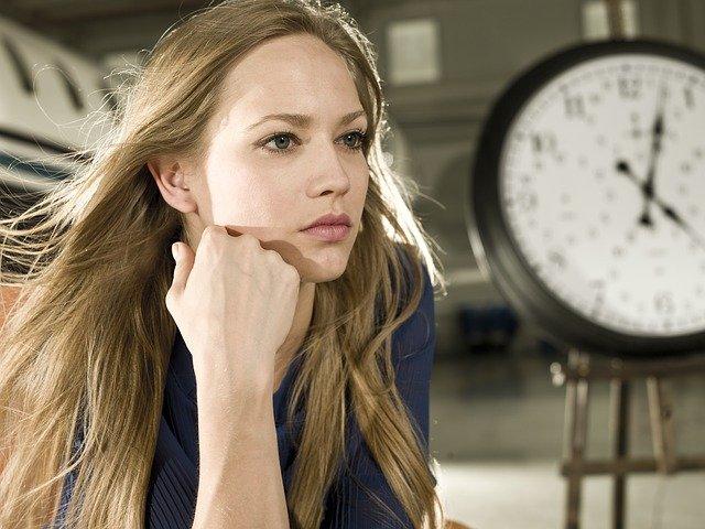 blondynka w rozpuszczonych włosach patrzy zamyślona w dal a obok wisi duży zegar