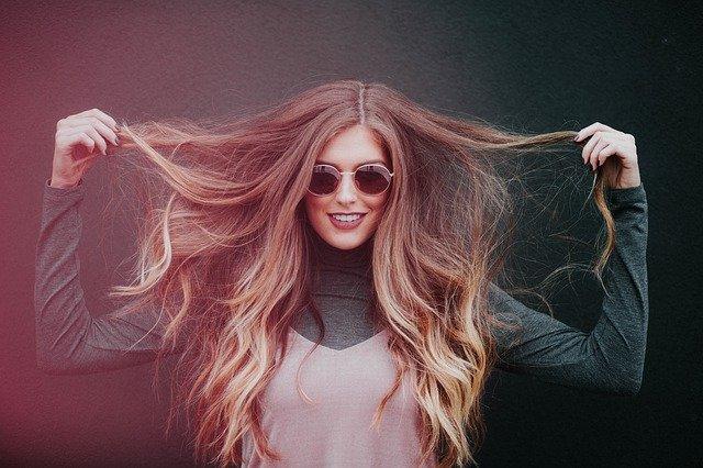blondynka z długimi włosami w ciemnych okularach uśmiecha się szeroko