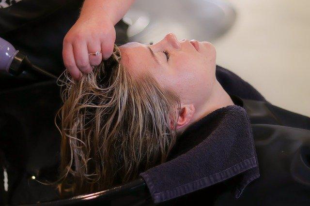 blondynka z zamoczonymi włosami u fryzjera w myjce