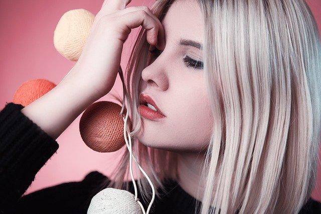 blondynka w long bobie z kolorowymi bombkami przy twarzy