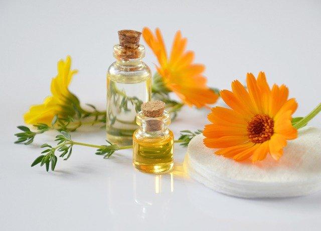 żółty płyn oleisty w szklanych butelkach przy żółtych kwiatach