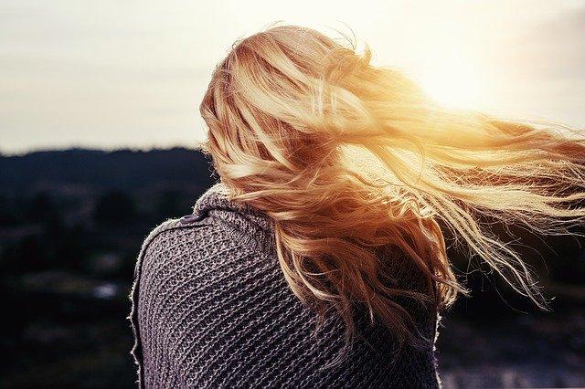 blondynka stoi tyłem w szarym swetrze