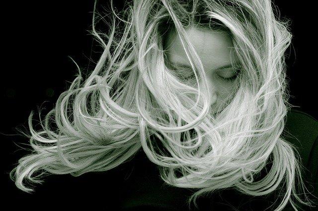 czarno-białe zdjęcie blondynki z włosami rozwianymi włosami na twarzy