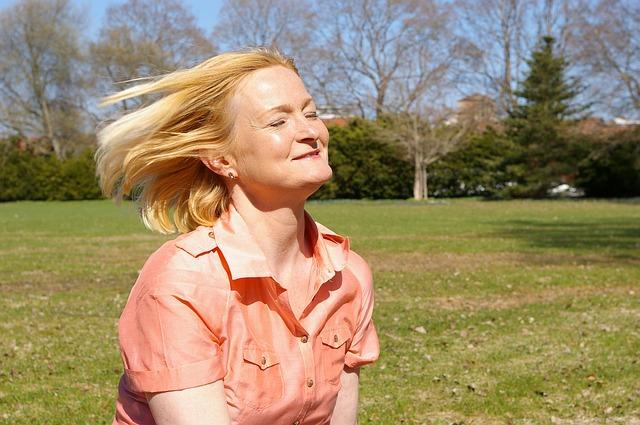 blondynka w rozpuszczonych włosach uśmiecha się na zielonej łące