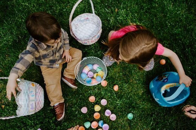 zdjęcie z góry dzieci, które bawią się kolorowymi jajkami, siedząc na zielonej trawie