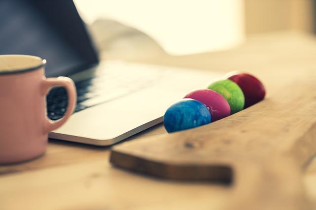 kolorowe pisanki ułożone tuż przed otwartym laptopem położonym na biurku