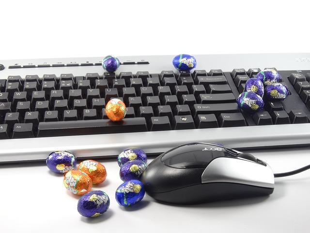pisanki położone na klawiaturze komputera i obok myszki do komputera