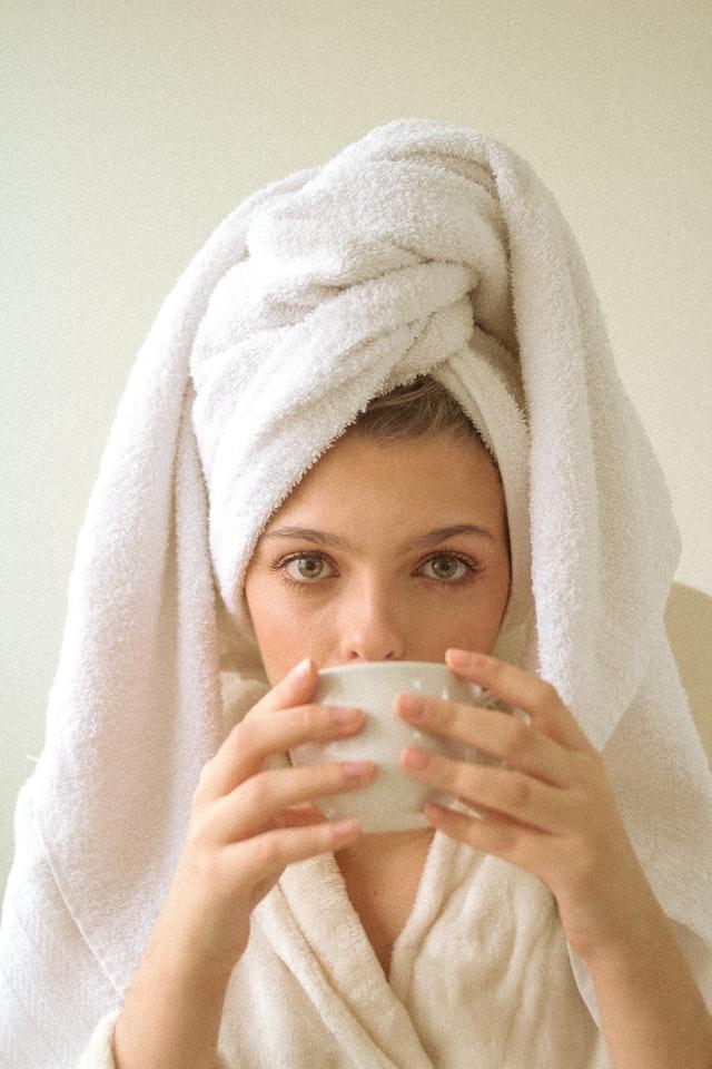 zblizenie na twarz kobiety w białym ręczniku na głowie, która pije coś z białej filiżanki