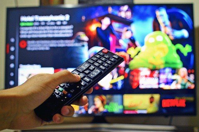 pilot telewizyjny na tle włączonego telewizora