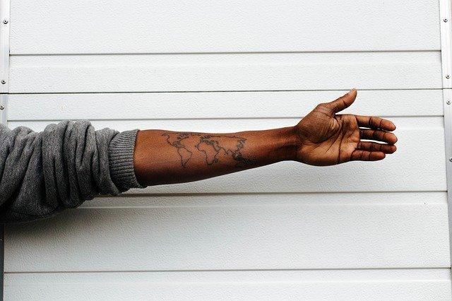 ręka w szarej bluzie z tatuażem na białym tle