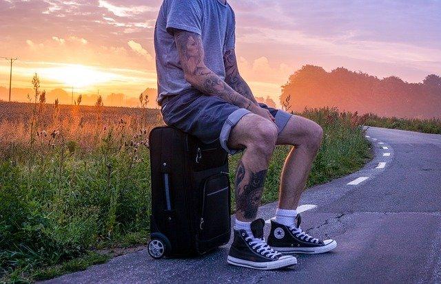 mężczyzna w krótkich szortach i szarej koszulce i w tatuażach siedzi na walizce