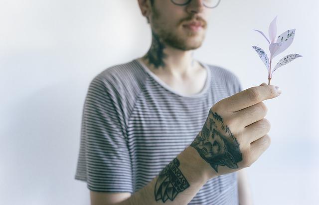 mężczyzna z brodą w koszulce w paski z tatuażem na dłoni