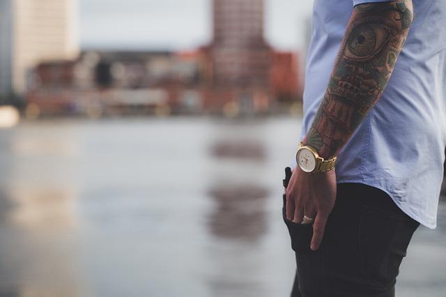 mężczyzna stojący bokiem z tatuażem na ręce i z zegarkiem na tle wody