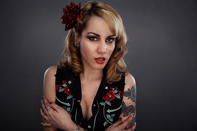 blondynka z kwiatem we włosach, pełnym makijażu, dekolcie i tatuażu na ręce