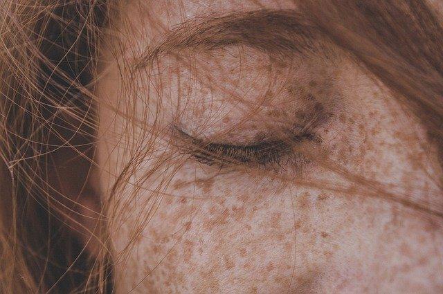 zbliżenie na zamknięte kobiece oko i piegi na twarzy