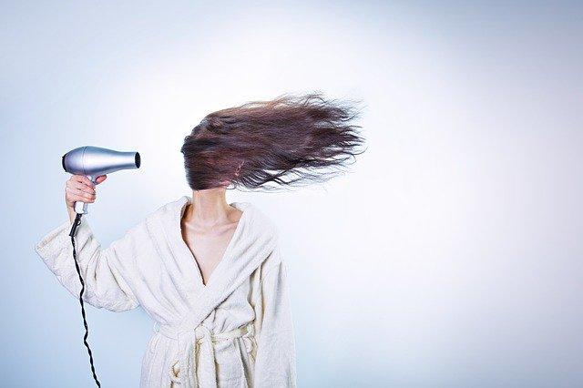kobieta w jasnym szlafroku suszy długie włosy, które zasłaniają jej twarz