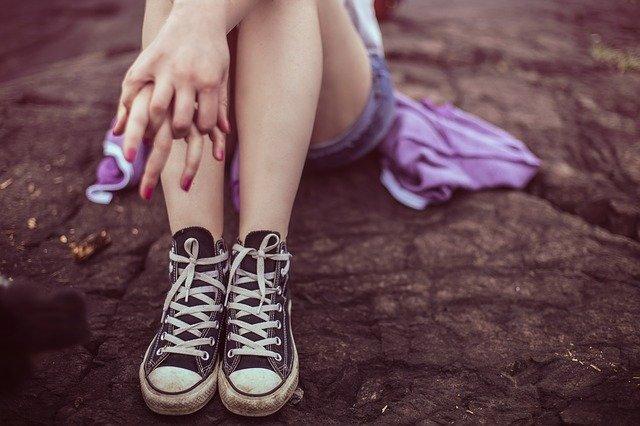 zbliżenie na stopu w trampkach, które należą do kobiety siedzącej w fioletowej sukience na skale