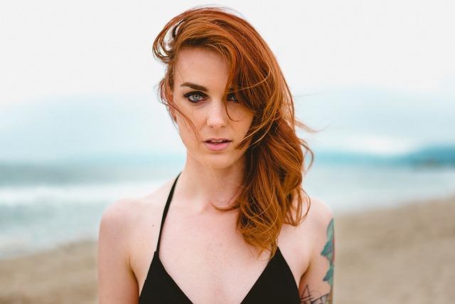 rudowłosa kobieta w czarnym kostiumie kąpielowym z tatuażem na ręce na tle morza