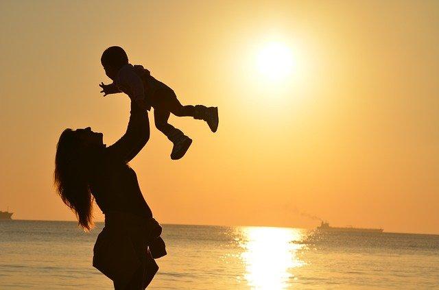 cień kobiety z małym dzieckiem trzymanym w powietrzu na tle zachodu słońca