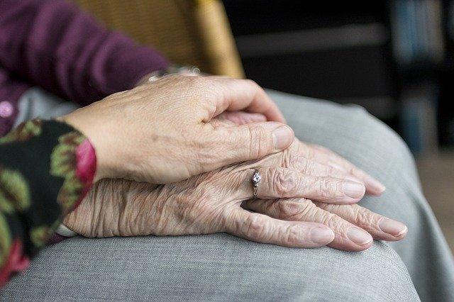 kobieta trzyma dłoń starszej kobiety w zbliżeniu